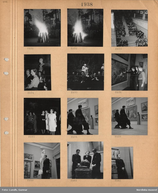 Motiv: Folksamling utomhus i kvällsljus runt en brasa av stora stående vedträn, publik sitter i Nationalmuseums stora trappa, skulptur, tre pojkar tittar på en tavla, tre unga kvinnor i finkläder, unga män sitter i en museisal med tavlor på väggarna, pojke står i museisal bredvid en kvinnoskulptur, tre pojkar tittar på en mindre skulptur av ett djur.