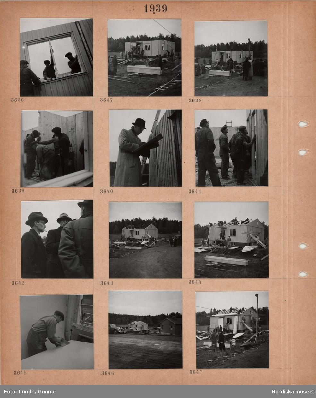 Motiv: Byggarbetsplats, resning av väggar och takstolar till ett småhus, arbetare, byggmaterial, tjänstemän i rock och hatt, väg.