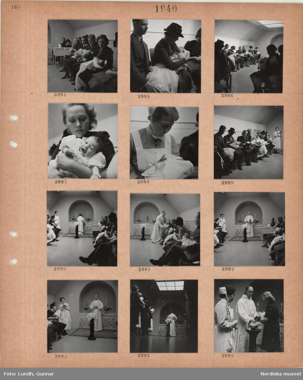 Motiv: Sittande kvinnor och män med spädbarn i famnen, kvinnor i sköterskeuniform, präst vid enkelt altare, dopfunt.