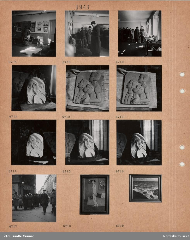 Motiv: Auktionslokal med utställda möbler, tavlor på väggarna, kunder, husgeråd, skulpturrelief av manshuvud, relief av tre barn i profil, gata med gående, personer i kö framför konfektaffär, inramad målning av naken kvinna vid soffa, inramad målning av havsvågor vid stenig strand.