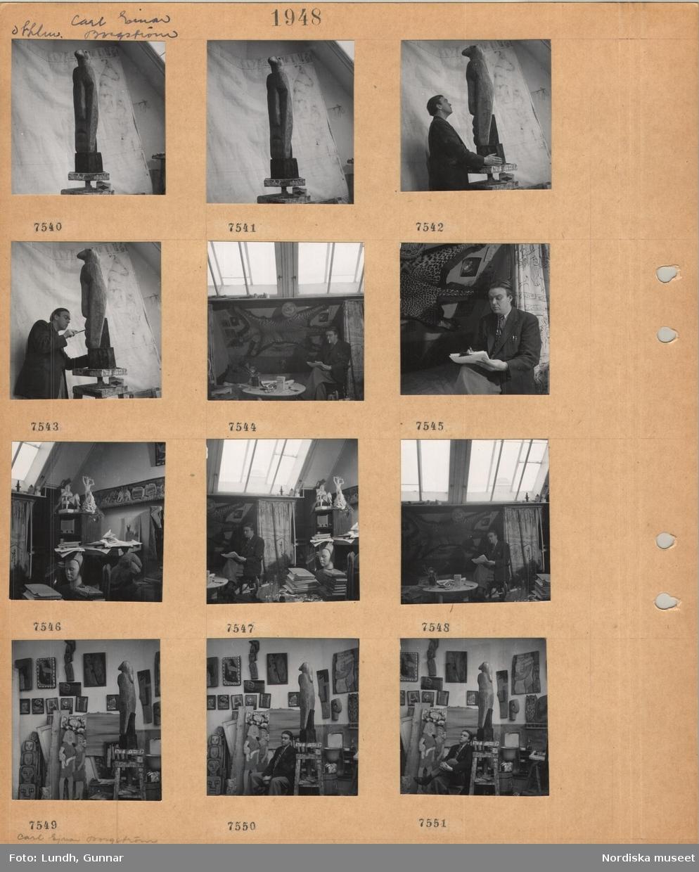 Motiv: Stockholm, Carl Einar Borgström, ateljé, skulptur av trä, avlångt ansikte med fågelhuvud överst, en man står med en skulptur, en man sitter och skriver med cigarett i munnen, leopardskinn på väggen, diverse skulpturer, radio i en hylla, konstnären sitter omgiven av konstverk.