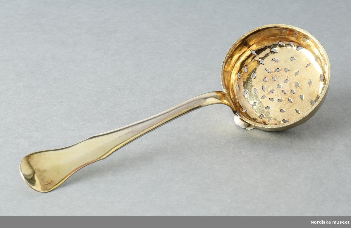 Strösked för socker. Jacob Lampa (1757-1787) 1789. Rund skopa med skaft. Skopan har svagt utvikt mynning, botten är perforerad med droppformade hål. Skaftet är böjt uppåt från skopan, vidgas mot den fiolformade, uppåtböjda änden. Inskriptioner på skaftets undersida: D.D. och därunder F.L.M. i skrivstil. /Kersti Wikström 2012 /Annika Tyrfelt 2017