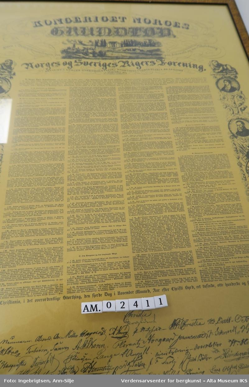 """Innmrammet """"Norges Grunnlov"""" 1814 med glass og brun ramme. Plakat av grunnloven fra mai 1814 med forandringene fra november samme året. Dekor med bilde av Eidsvoldmenn, engler, løver og blomster."""