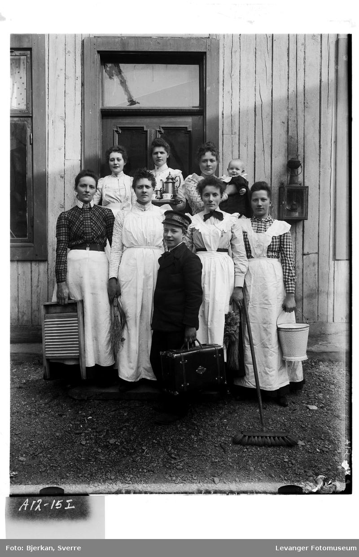 Gruppe kvinner  utstyrt med bøtter og vaskebrett, kaffeservise, og en gutt med reiseveske.