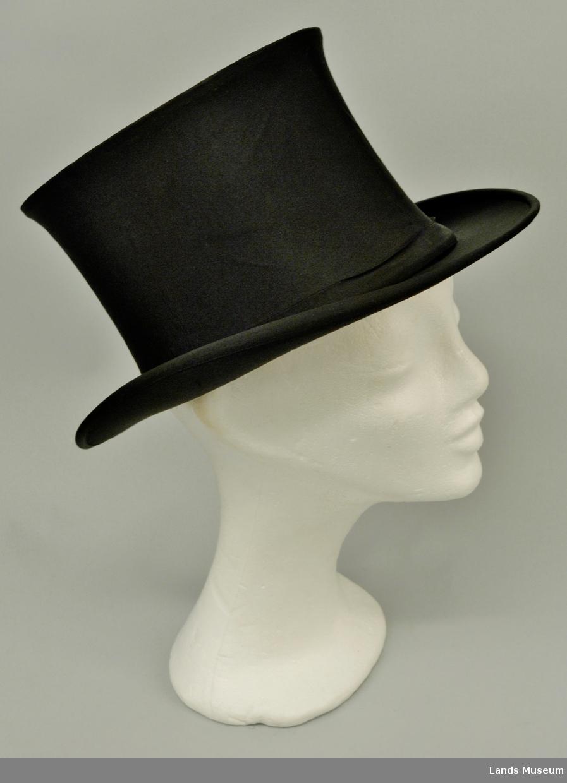 Svart rips av natursilke. Sammenleggbar. Hatten er oval med en oval smal eske.
