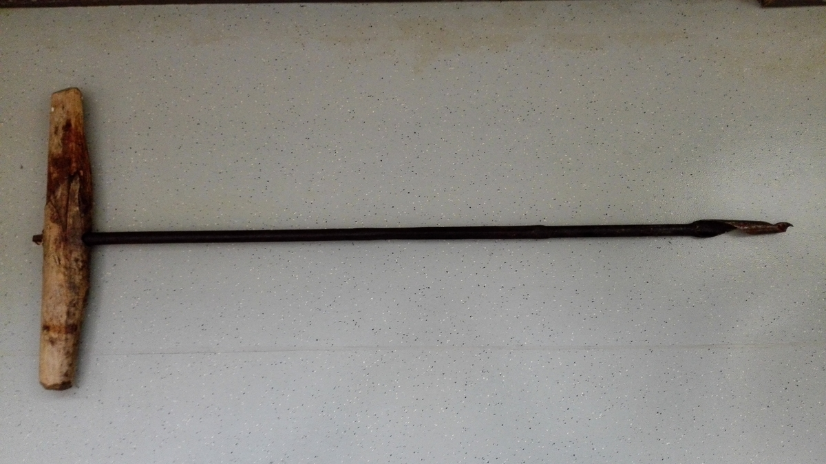 Lang navar som går inn i eit  fast trehandtak. Navaren har merke etter å ha vore skøytt, eller reparert to gonger. Navaren består tydeleg av tre ulike delar.