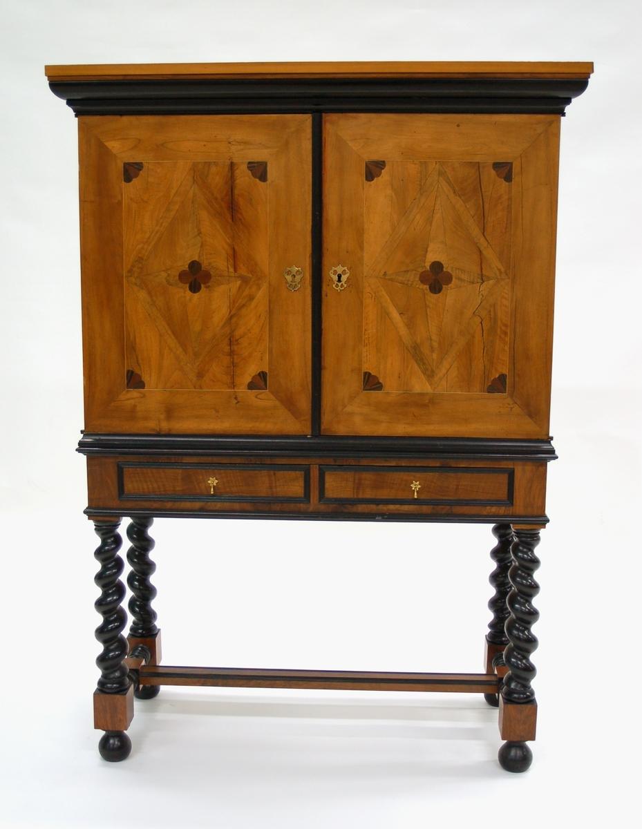 Acc. kat: Kabinettskåp av valnöt, kring smålådor och fack, hopplister, inläggningar, nedtill 2 st smålådor, fotställning med vridna ben.
