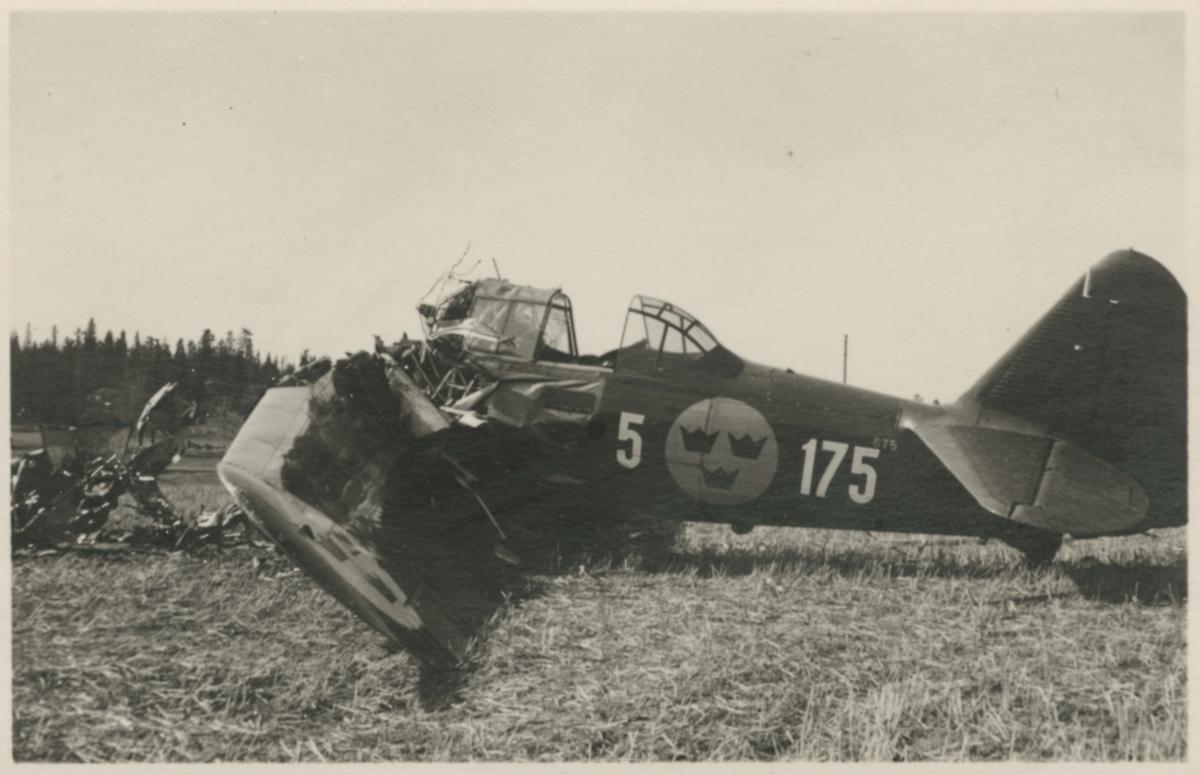 Havererat militärt skolflygplan SK 14 nummer 675, märkt F 5-175 på ett fält utanför Vittsäter, sydost om Nykil i Östergötland, den 30 april 1940. Män i närheten av flygplanet. Serie om 8 bilder.