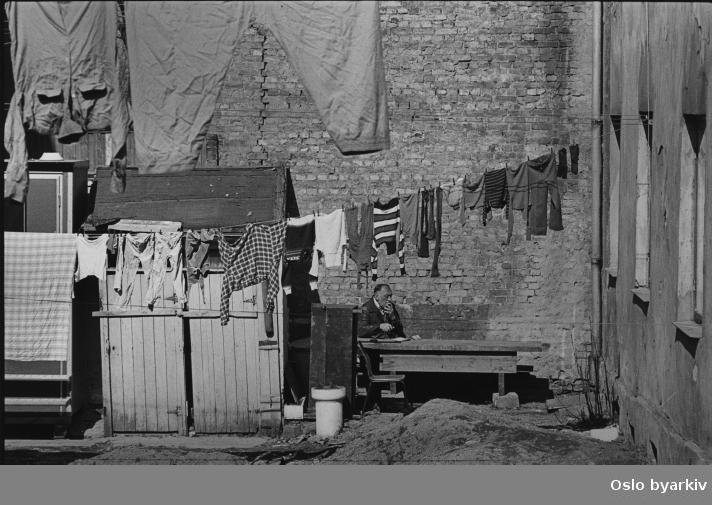 Klesvask til tørk i bakgården i Heimdalsgata 36. En mann tar seg en pause. Fotografiet er fra prosjektet og boka ''Oslo-bilder. En fotografisk dokumentasjon av bo og leveforhold i 1981 - 82''. Kontakt Samfoto ved ev. bestilling av kopier..Fått tilbakemeldning fra en som er oppvokst i Heimdalsgata 36, at dette må være bilde av Heimdalsgata 38 på grunn av utedoen på bildet.
