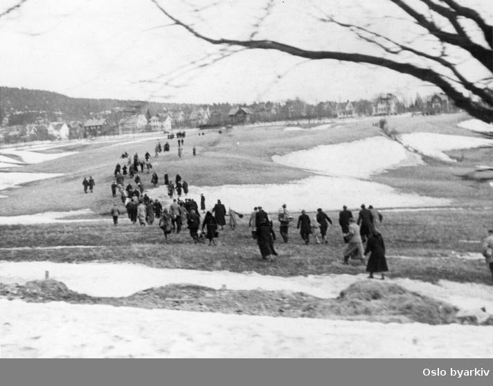Panikkdagen 10. april etter rykter om bombing av Oslo fra britiske bombefly. Presis klokken 11.30 onsdag 10. april 1940 gikk flyalarmen. Folk på flukt over Muselunden ovenfor Sinsenkrysset, på vei mot Nordre Åsen ved Grefsen. Grefsenåsen og Lillomarka i bakgrunnen.