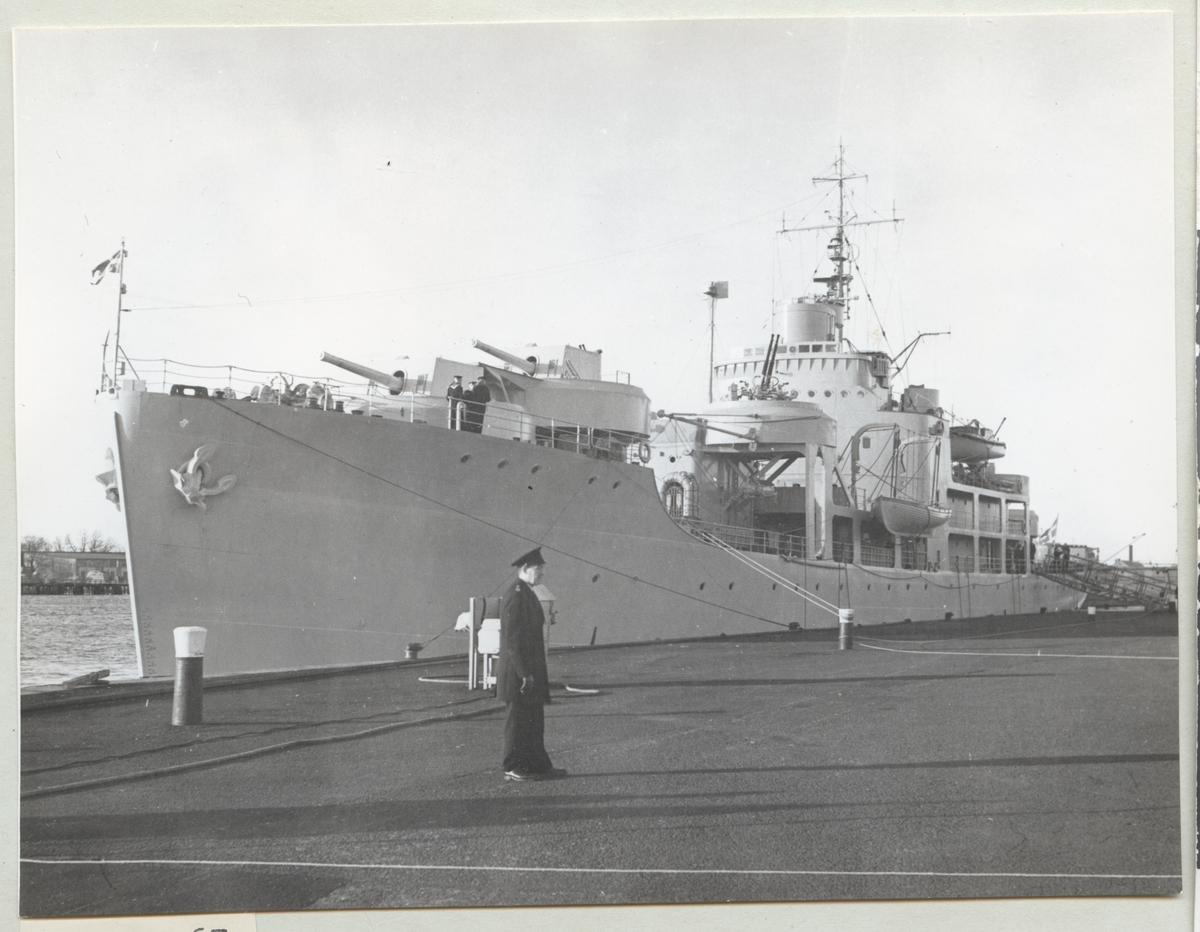 Bilden visar minfartyget Älvsnabben från babordssida framifrån som ligger förtöjt i hamnen. I förgrunden står en ensam marinsoldat på kajen.