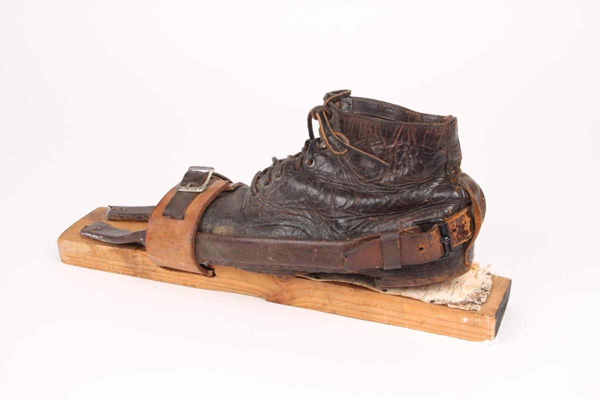 En skibinding med tåstropp og bakbinding av lær. Tåstroppen er bred og lukkes med en lærstropp med metallspenne. Tåstroppen går gjennom bindingshullet. Bakbindingen er festet med skruer foran skoen oppå skien. Den består av to stive bøyler dekket i lær på hver side av skoen, som går under tåstroppen langs skoen. En lærstropp er sydd på den ene bøylen og festes til den andre med en metallspenne. Fotstegplate i bjørkenever. Beksømstøvel med en løkke bakpå støvelen til å holde bakbindingen fast på skoen.