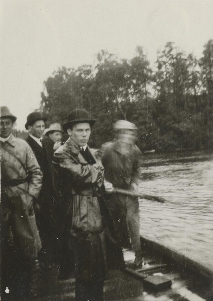 En grupp män samlade vid vatten.