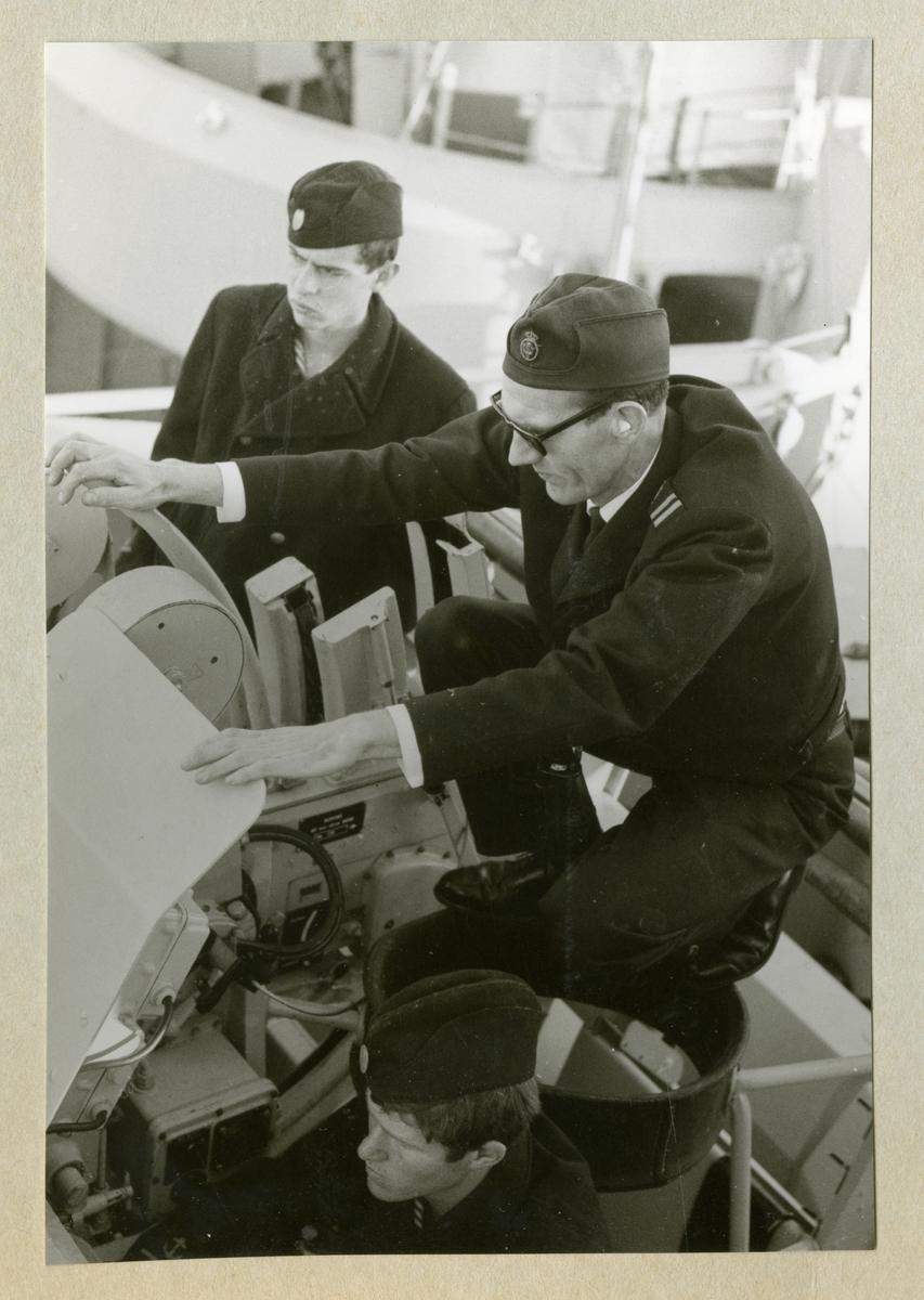 Bilden föreställer tre uniformsklädda besättningsmän vid en artilleripjäs ombord på minfartyget Älvsnabben under långresan 1966-1967.