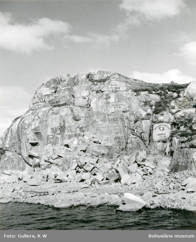 Bergvägg där man brutit sten, väggen är täckt med text, namn, ortsnamn, fartygsnamn och datum
