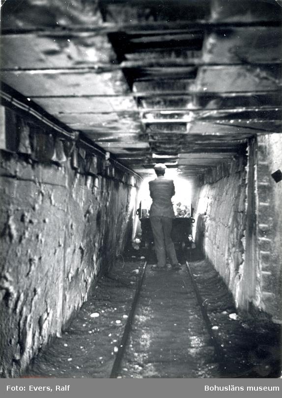En man går med en vagn fylld med gatsten i en tunnel