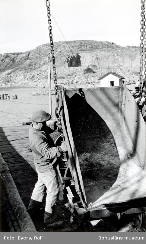 En man lossar en vagn som troligen fraktat gatsten till lastbryggan intill stenbrottet