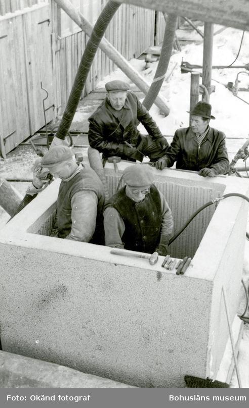 Ett stenbock som invändigt tagits ur så att det består av fyra sammanhängande väggar. Två män står nere i blocket och arbetar, två män står utanför och tittar på arbetet.