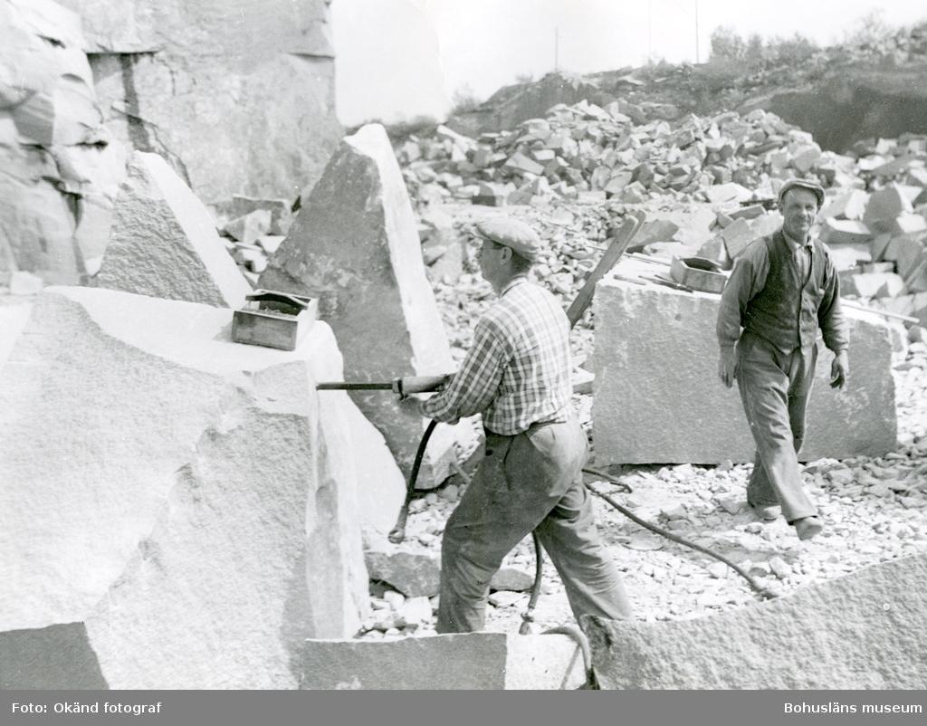 En man borrar i ett stenblock, en leende man passerar