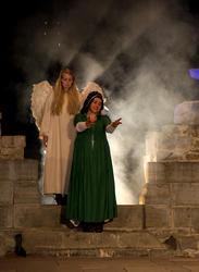 En hvit engel står i en røyksky bak Jomfru Karine som strekker armene fram. (Foto/Photo)