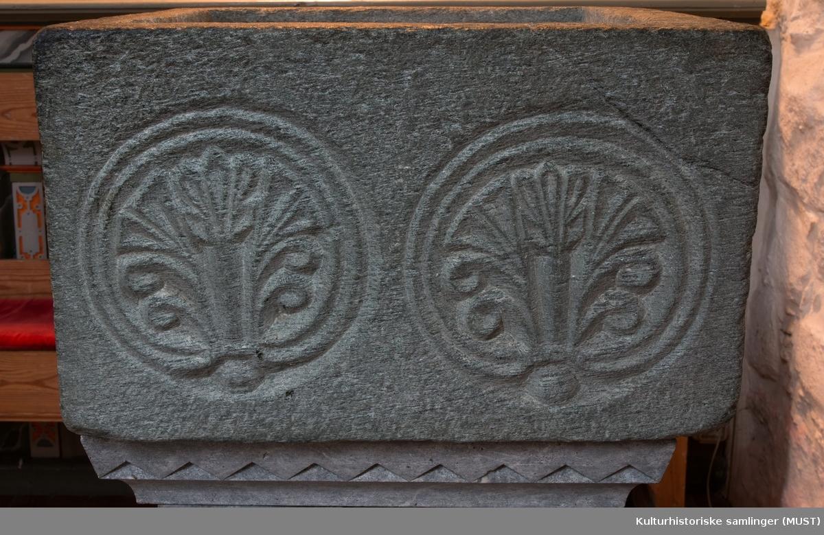 Et mønster bestående av to sidestilte palmetter inni hver sin sirkel , sees på hver side av den kvadratiske døpefontens øvre del. Enkelte steder sees også tegn på at det originalt har gått en mønster/dekorlinje langs nedre kanten.