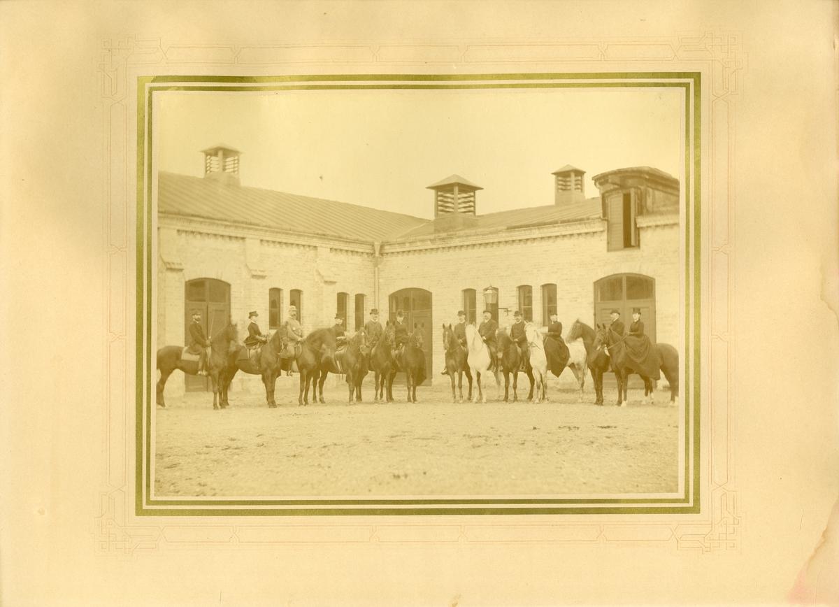 Kvinnor och män till häst utanför stallbyggnad.