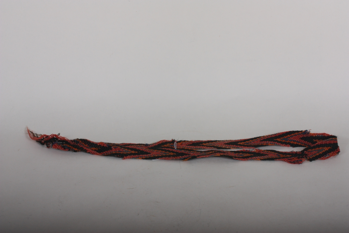Pøsa/fletta/fingra band, usikkert om det har original lengd. I eine enden falda, i andre enden lause trådar.