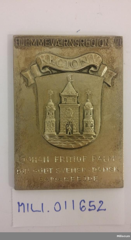 Hedersplakett i valören silver, tillverkad av försilvrad brons, med tillhörande etui.