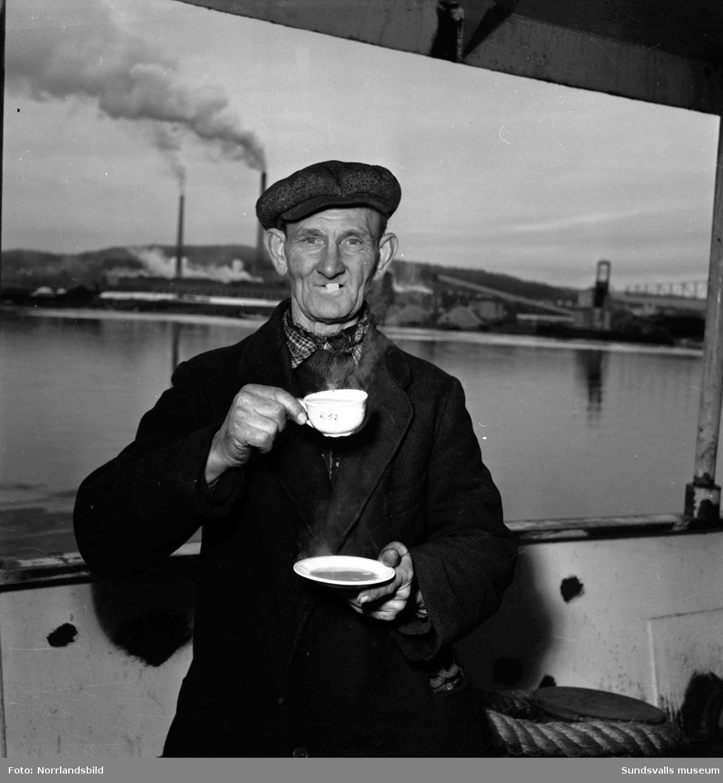 En man vid Skönviks sågverk dricker kaffe på bit. I bakgrunden syns Östrandsfabriken.