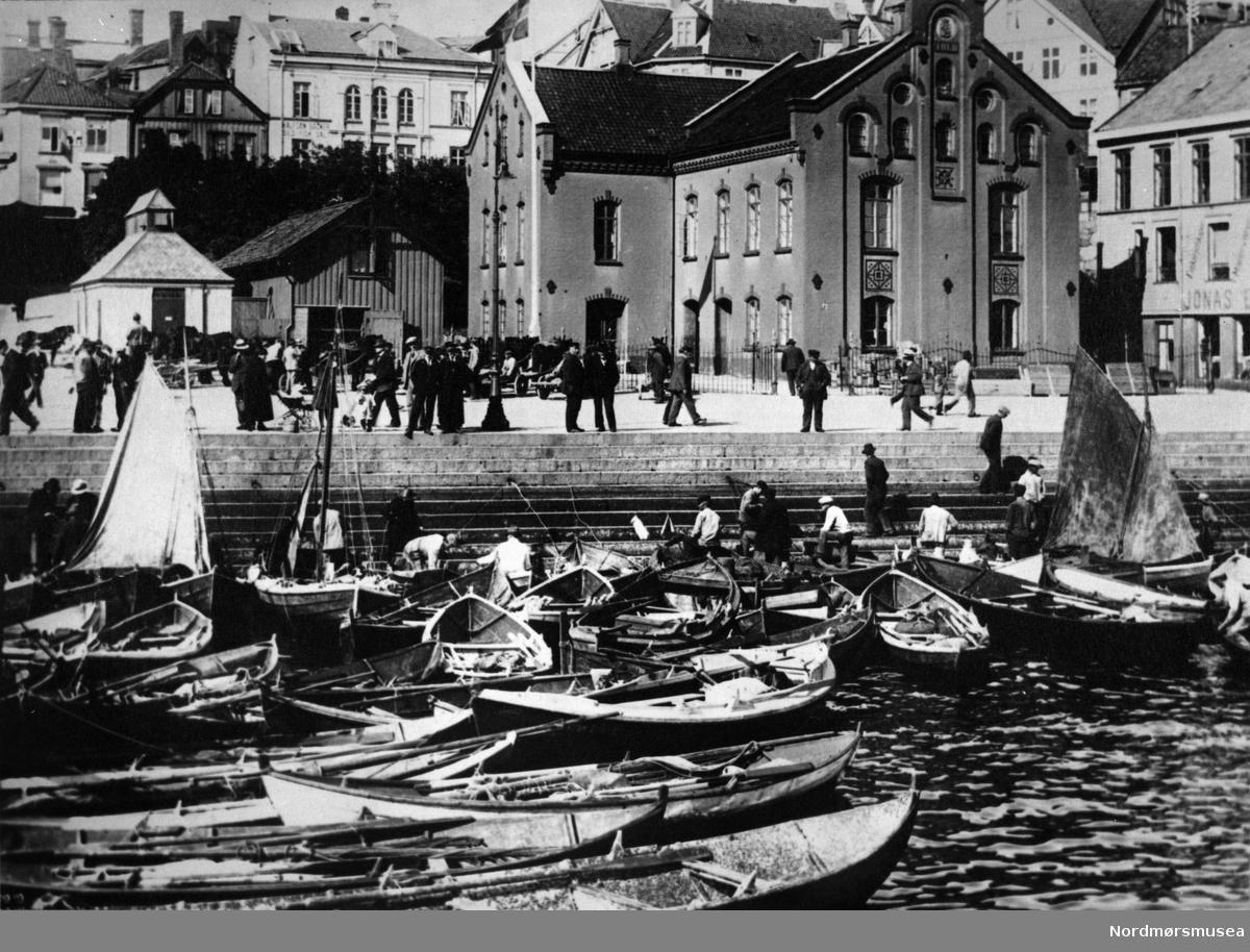 Halfdan Backer, Sild, Fisk, Salt står det på skiltet bak Tollbua (etter krigen Grungbakken). Kristiansund ca 1920. Fisktrappa, geitbåter, fiskere, Trafokiosk, seil, Nordmøre museums fotosamling.
