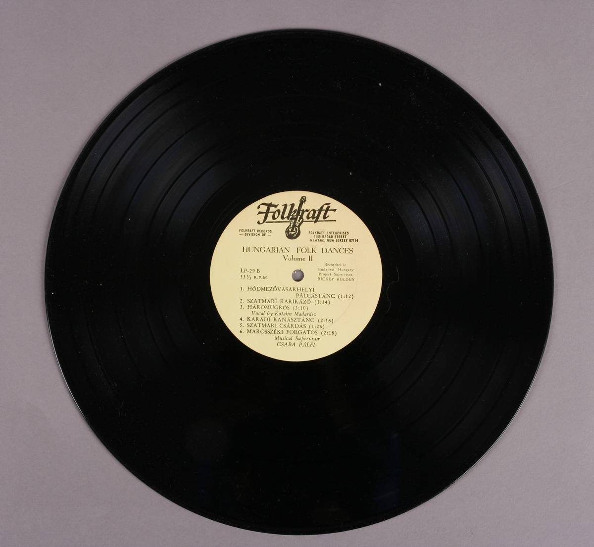 Grammofonplate i svart vinyl med plateomslag av papp. Platen ligger i en papirlomme. Ligger også ved et stiftet hefte (se bilde).