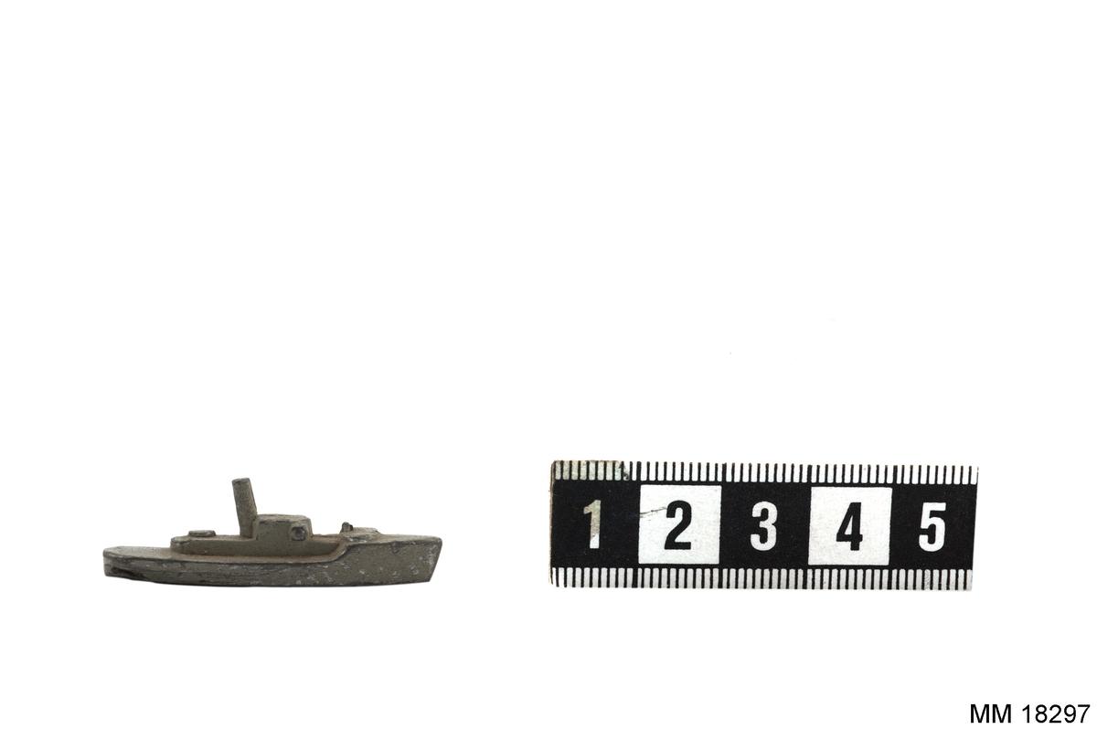 Fartygsmodell gjuten av metall i ett stycke, målad i grått. Spetsig, hög för och lägre, tvärskuren akter. Plan botten. Mast. Mindre båttyp.