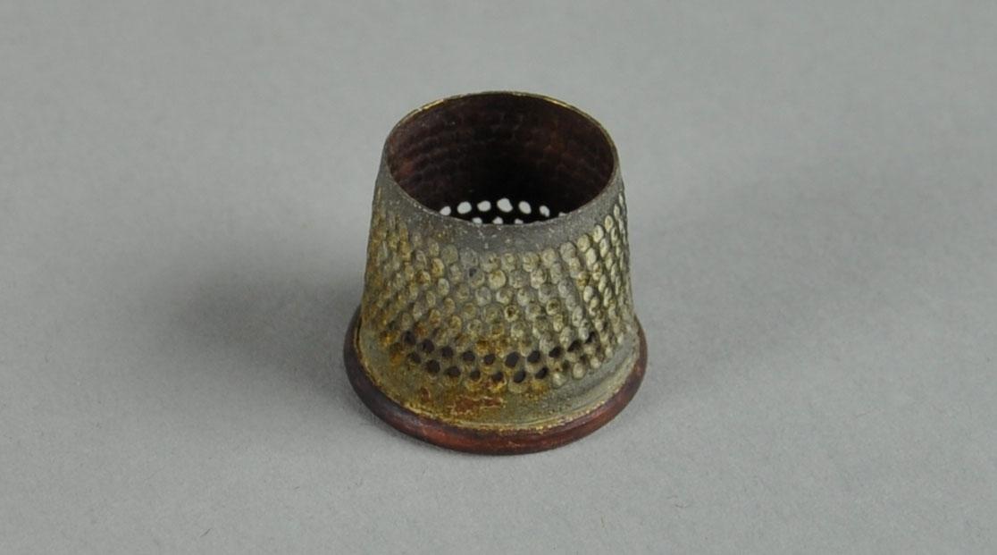 Fingerbøl av metall, med ring av messing. Fingerbølet har innfelte rader av prikker på utsiden for bedre feste.