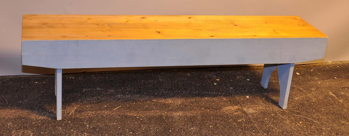 Benk hvor sitteflaten er trehvit, og sideplater og understell er malt blå. Understellet på benken er sveifet.