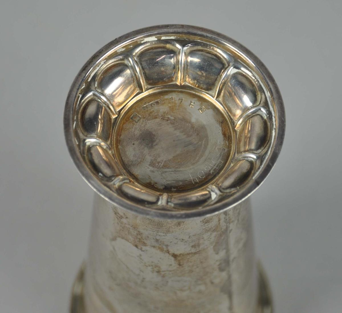 Sylinderformet pokal av sølv, på stett. Stetten har dekor av perlerad.