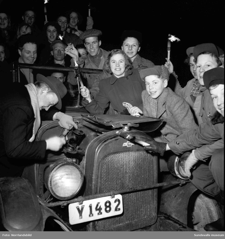 Skönvik-Sunds socialdemokratiska ungdomsklubb (SDUK) samlade kring en gammal Chevrolet från 1926. Motorhuven är öppen och en del av ungdomarna har facklor i händerna.