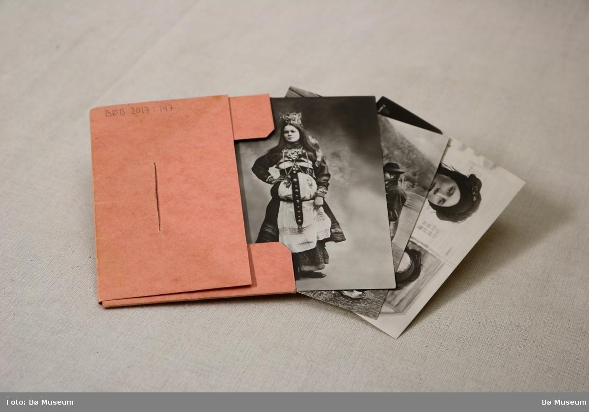 Lita mappe/konvolutt med 10 fotografi som syner modellar i norske folkedrakter. Framsida har eit stempla frimerke til 20 øre. Baksida syner logoen til firmaet Mittet & Co.
