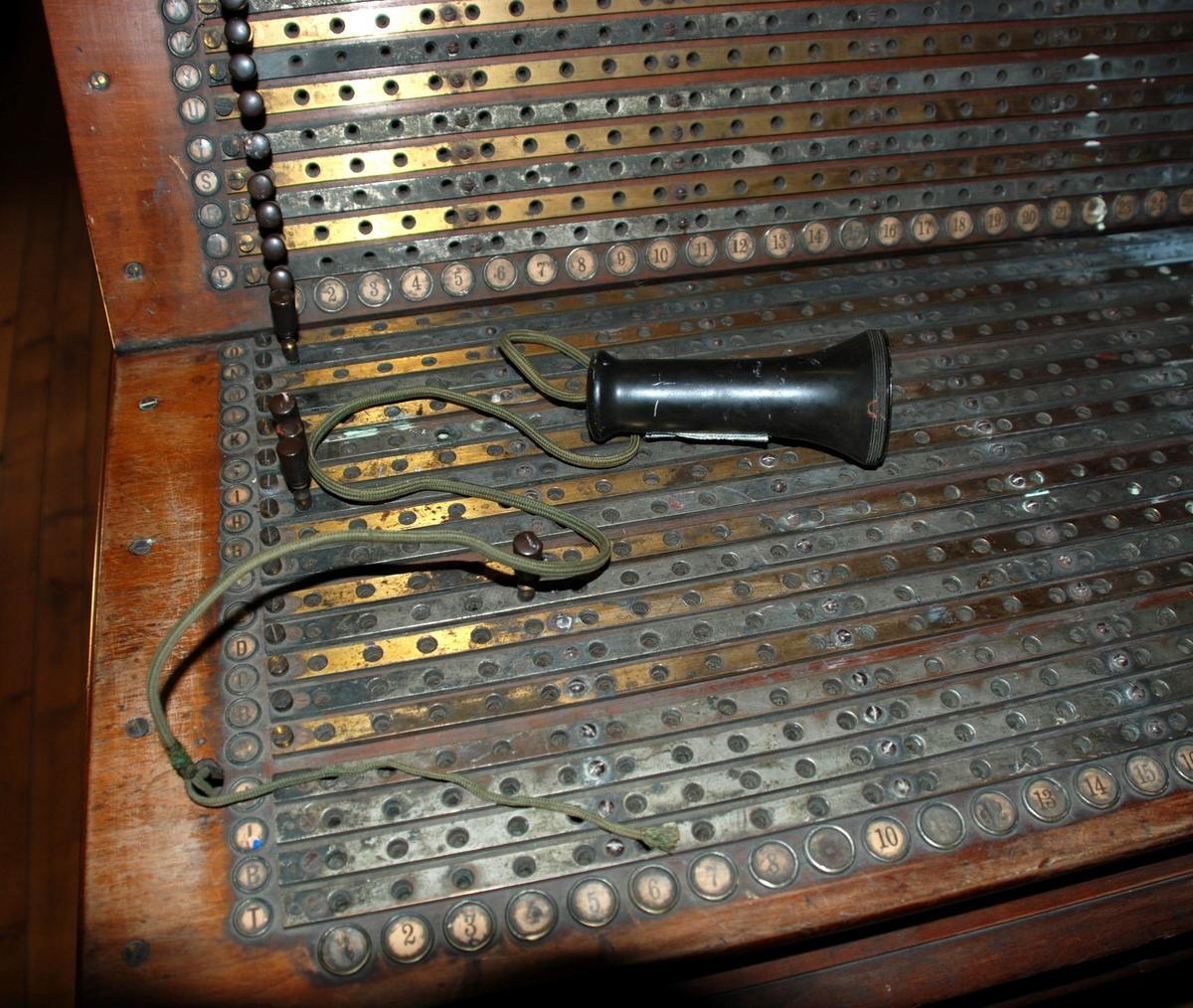 Koblingsbord for telefonsamtaler. Sentralbordet er montert på understelll av tre med fire dreide ben med bensprosse i H-form. Toppen har utskjæring i tre. Koblingspanelet er i metall, der kontaktpunktene er merket med bokstaver loddrett og tall vannrett. Mikrofon festet på svingstang øverst på panelbordet,, telefonrør i bakelitt.