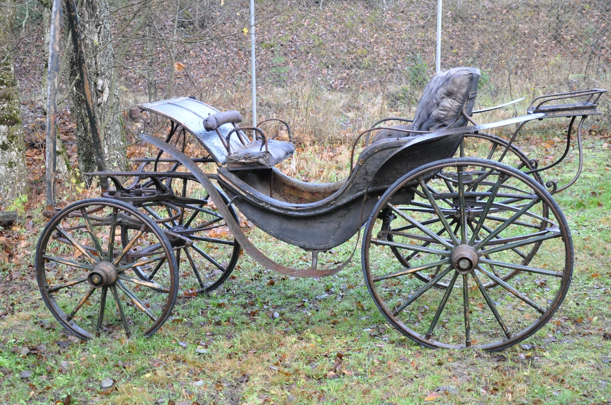 4-hjuls vogn for trekk med én hest. Trilletype. Spesielt stor fløy (skvettskjerm) . Lakeisete bakerst, stort hovedsete, lite motsete.