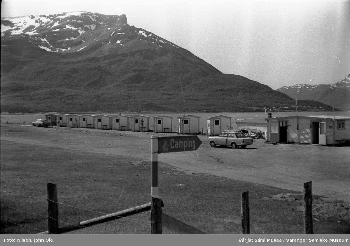 Campingplass i Skibotn området. Skilt i forgrunnen, hav og fjell med snødekt topp i bakgrunnen. 17. juli 1967