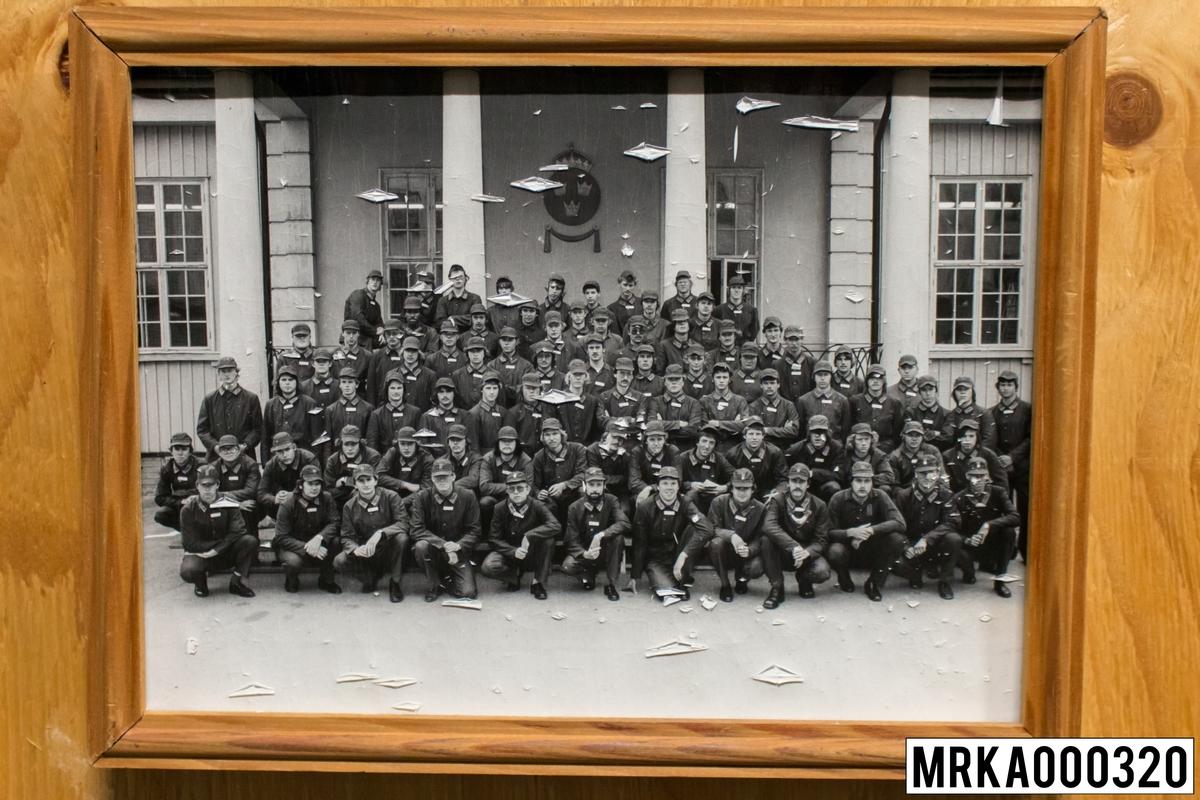 Fotografi taget på befäl och soldater som genomfört grundläggande soldatutbildning på 1:a Batteriet KA 2. Fotografiet taget utanför gymnastikhallen på Gräsvik KA 2.