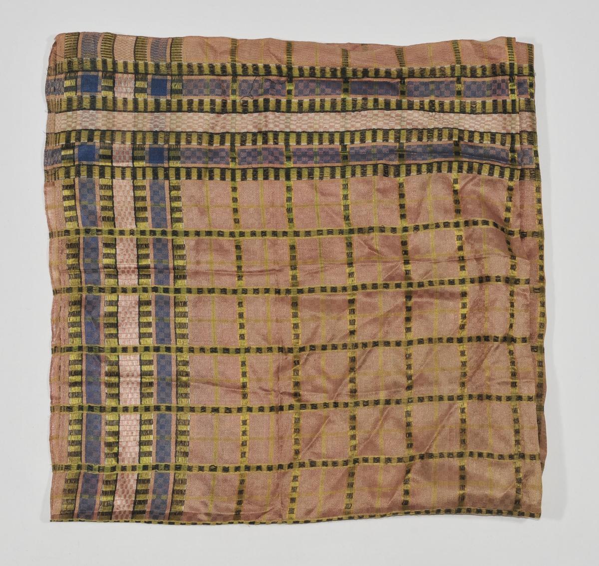 Silketørkle vevd i ruter i lys rosa, lilla, grønt og brunt. Smal falda på to sider, jarekant i dei to andre. Kjerringtann bord rundt.