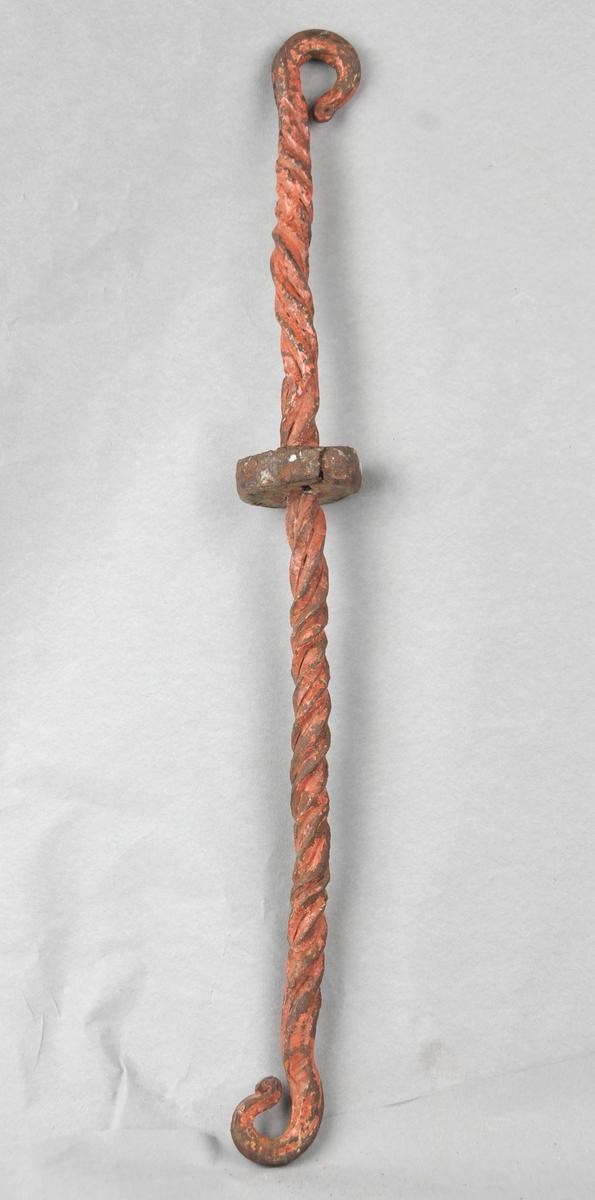 Lampeoppheng av fire jernstenger  smidde saman til ei vridd stong med smidde festekrokar i kvar ende. Omlag midt på stonga er det tredd på og festa ei rund skive.