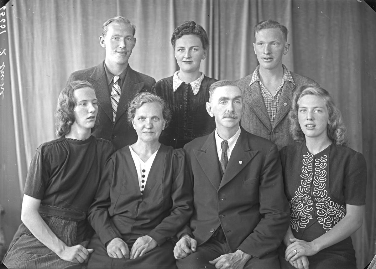 Gruppebilde. Familiegruppe på syv. Eldre kvinne, eldre mann, to unge menn og tre unge kvinner. Bestilt av Karl Håkansen. Vestegt. 83.