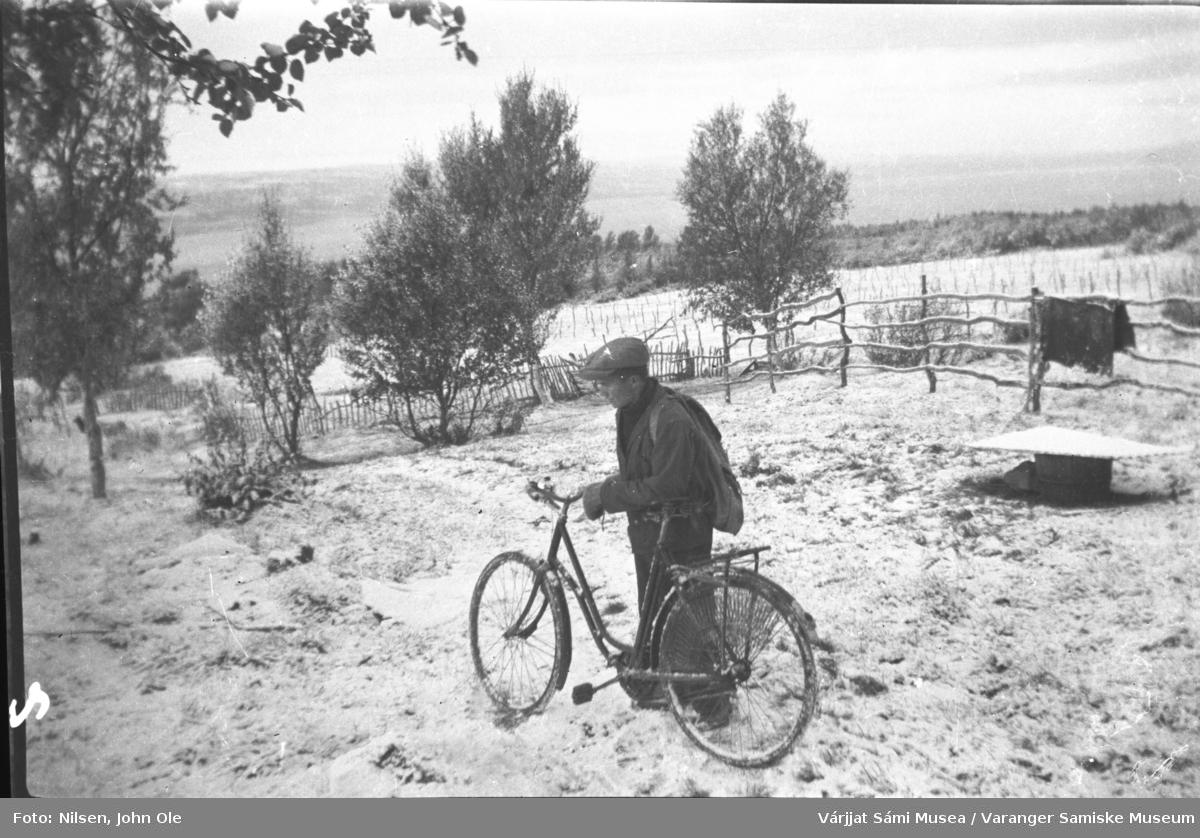 Nils Anders Nilsen på sykkel i Fuoitnjárga / Bunes på 1940 tallet. Ser ut som første snøfall. Angsnes i bakgrunnen.