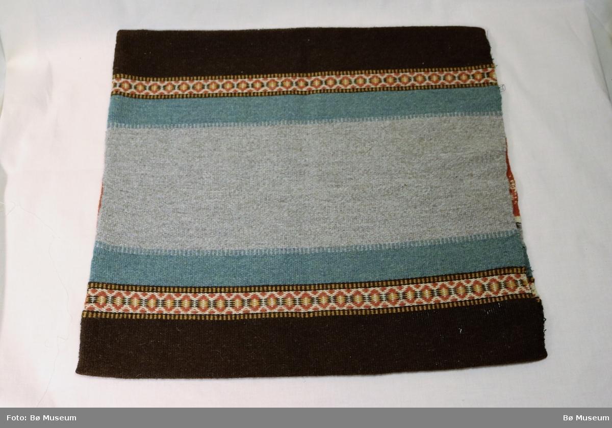 """Putetrekk med mønster som består av stilisera blomar, striper i vestfoldteknikk, rosengang og toskaft. Sydd saman i to av siden, """"bukt"""" i den treie, åpning i den fjerde."""