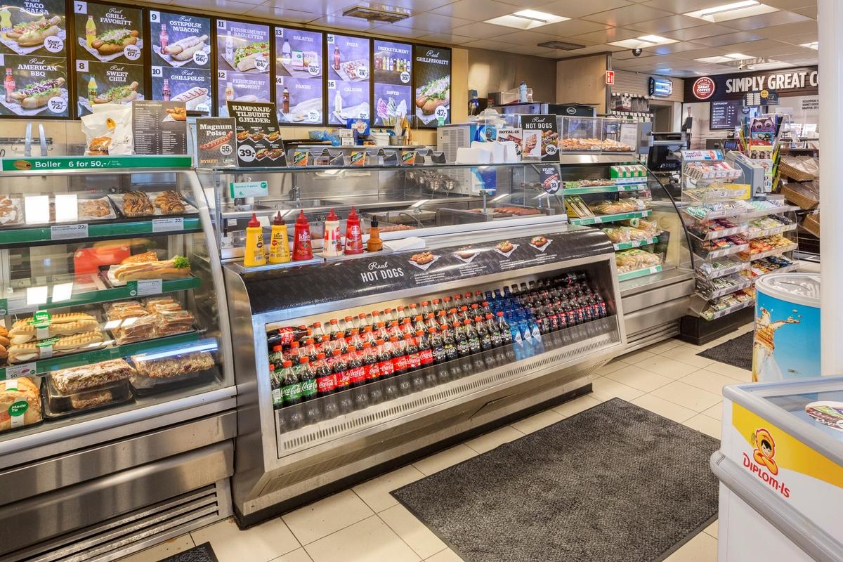 Statoil Dal. Butikk interiør med butikkdisk med varme pølser, ketchup og sennepsfalsker.  Reklameskilt på veggen bak butikkdisken  Leskedrikker på en glashylle foran på butikkdisken.