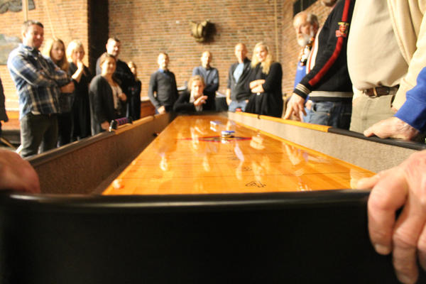 Shuffleboard i vestibylen på Norsk Maritimt Museum, nærbilde av den ene enden, mange folk rundt.. Foto/Photo