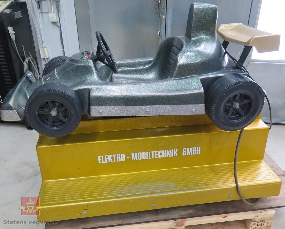 Elektrisk/mekanisk lekebilautomat som beveger seg når man putter på penger (5 kr). Bilen er lakkert med grønn flake lakk, sokkelen med gull flake. Merking fra produsenten.