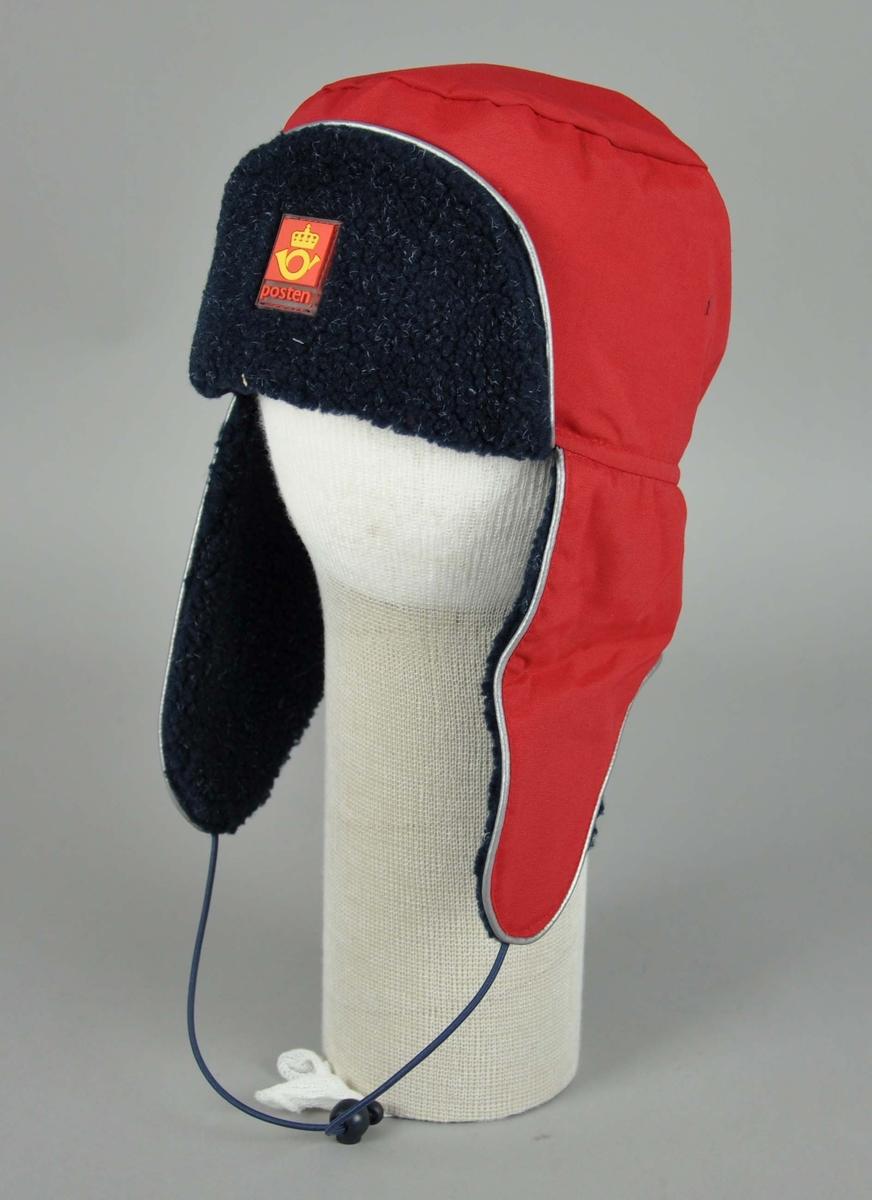 Rød vinterlue med sort foring på innerside. Øreklaffer og strikk.